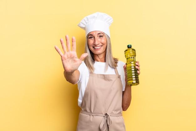 Mulher chef de meia-idade sorrindo e parecendo amigável, mostrando o número cinco ou quinto com a mão para a frente, em contagem regressiva