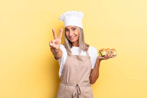 Mulher chef de meia-idade sorrindo e parecendo feliz, despreocupada e positiva, gesticulando vitória ou paz com uma mão segurando uma caixa de ovos