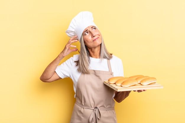 Mulher chef de meia-idade sorrindo feliz e sonhando acordada ou duvidando, olhando para o lado e segurando uma bandeja de pão