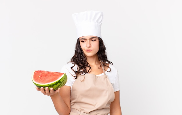 Mulher chef hispânica bonita se sentindo triste, chateada ou com raiva, olhando para o lado e segurando uma melancia