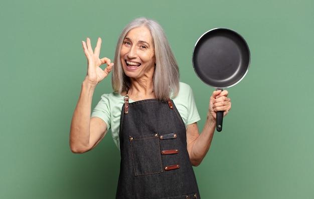 Mulher chefe de meia-idade com cabelos grisalhos e uma panela