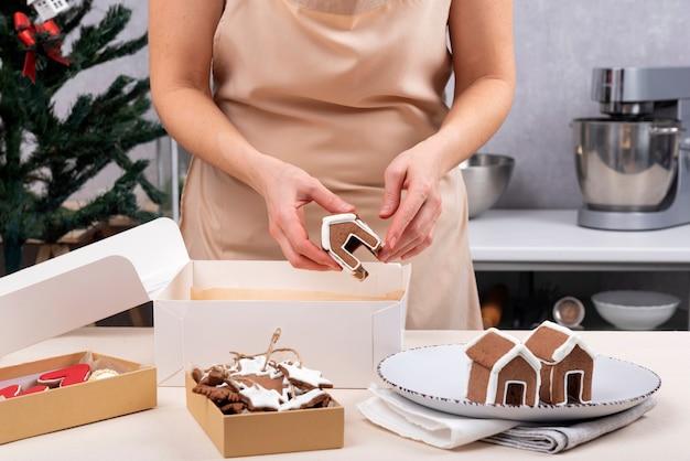 Mulher chefe de pastelaria faz casa de pão de mel. doces de natal para fazer bolos.