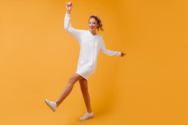 Mulher cheia de energia dançando em um estúdio aconchegante