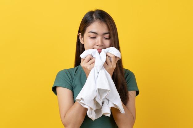 Mulher cheirando a roupa limpa depois de lavar