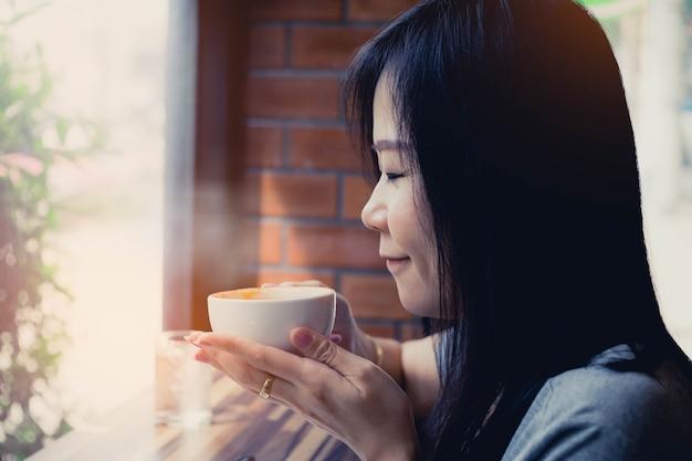 Mulher cheirando e bebendo chá quente com feliz.