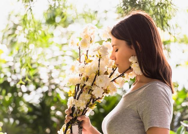 Mulher, cheirando, flores brancas