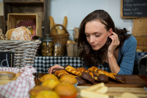 Mulher cheirando pão no balcão da padaria