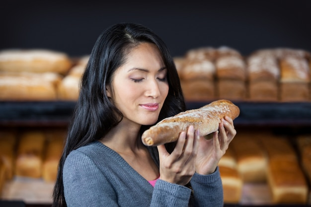 Mulher cheirando uma baguete