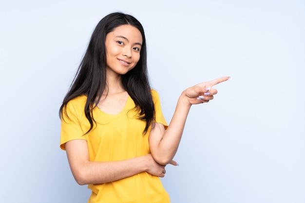 Mulher chinesa adolescente isolada em azul apontando o dedo para o lado