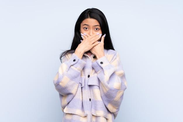 Mulher chinesa adolescente isolada em azul