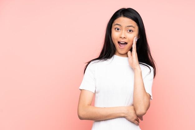 Mulher chinesa adolescente isolada em rosa com expressão facial surpresa e chocada