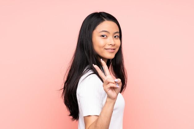 Mulher chinesa adolescente isolada em rosa sorrindo e mostrando sinal de vitória