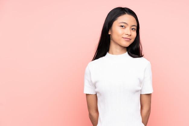Mulher chinesa adolescente isolada na parede rosa com dúvidas enquanto olha de lado