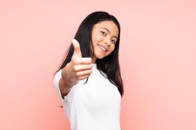 Mulher chinesa adolescente isolada na parede rosa com polegares para cima, porque algo de bom aconteceu