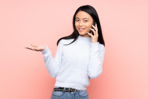 Mulher chinesa adolescente isolada na parede rosa, mantendo uma conversa com o telefone móvel com alguém
