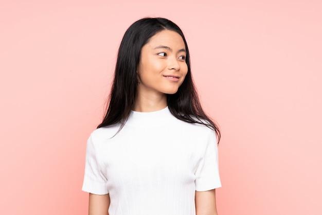 Mulher chinesa adolescente isolada na parede rosa, olhando para o lado e sorrindo