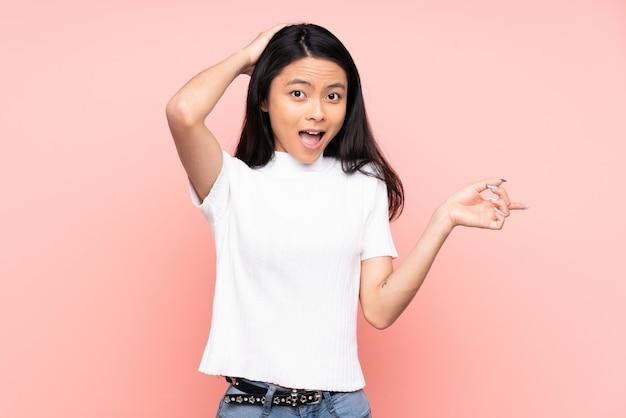Mulher chinesa adolescente isolada na parede rosa surpreendeu e apontando o dedo para o lado