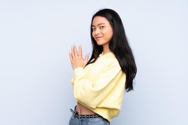 Mulher chinesa adolescente na parede azul planejando algo