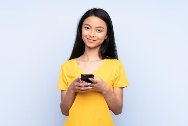 Mulher chinesa adolescente na parede azul surpreendeu e enviando uma mensagem