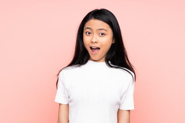 Mulher chinesa adolescente na parede rosa com expressão facial de surpresa