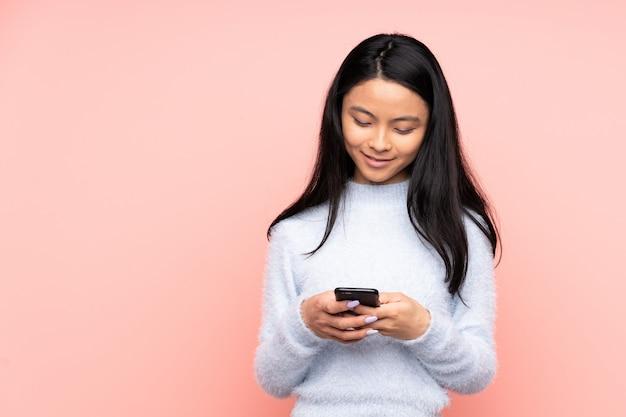 Mulher chinesa adolescente na parede rosa, enviando uma mensagem com o celular