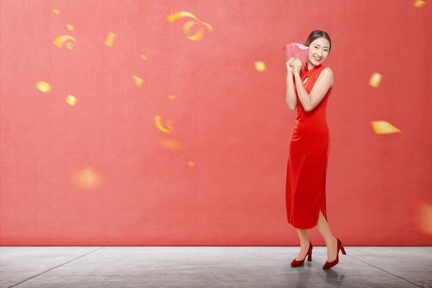 Mulher chinesa asiática em um vestido cheongsam segurando envelopes vermelhos