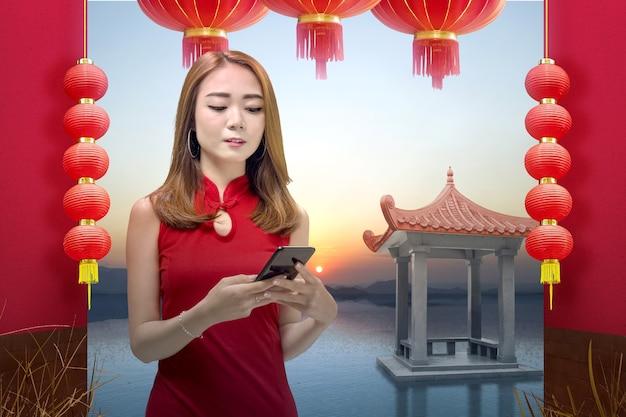 Mulher chinesa asiática em um vestido cheongsam segurando um telefone celular. feliz ano novo chinês