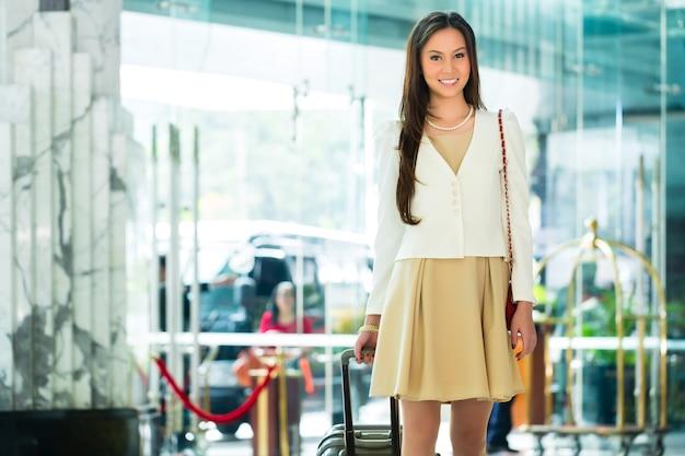 Mulher chinesa asiática na entrada do hotel chegando