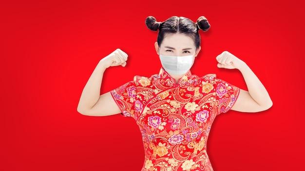 Mulher chinesa asiática na tradição de sheongsam vermelho suíte chiness com forte ação saudável com máscara facial em pandemia de coronavírus