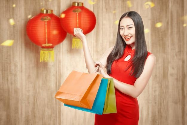 Mulher chinesa asiática no vestido cheongsam segurando sacolas de compras