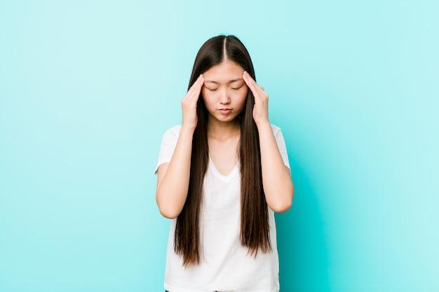 Mulher chinesa bonita jovem tocando templos e tendo dor de cabeça.