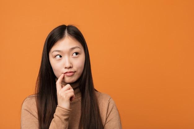 Mulher chinesa bonita nova olhando de soslaio com expressão duvidosa e cética.