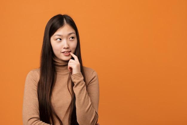 Mulher chinesa consideravelmente nova pensamento relaxado sobre algo que olha um espaço da cópia.