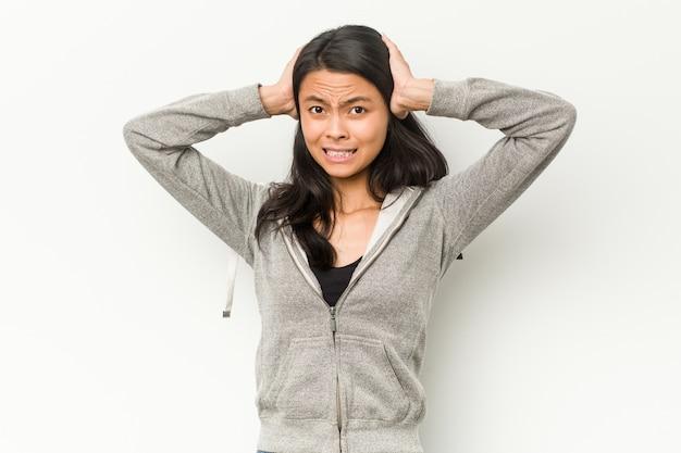 Mulher chinesa de aptidão jovem cobrindo os ouvidos com as mãos, tentando não ouvir som muito alto.
