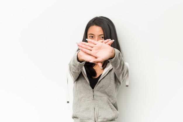 Mulher chinesa de aptidão jovem fazendo um gesto de negação