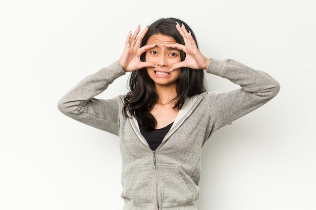 Mulher chinesa de aptidão jovem, mantendo os olhos abertos para encontrar uma oportunidade de sucesso.