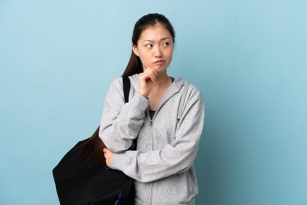 Mulher chinesa de esporte jovem com saco de esporte sobre azul isolado tendo dúvidas e pensando