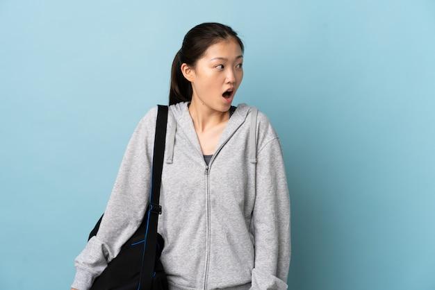 Mulher chinesa de esporte jovem com saco de esporte sobre parede azul isolada, fazendo o gesto de surpresa enquanto olha para o lado