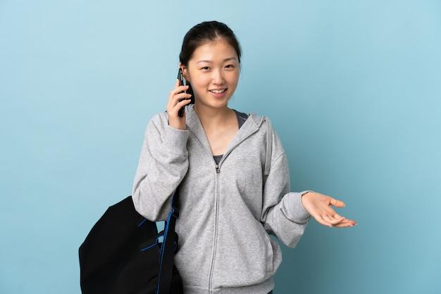 Mulher chinesa de esporte jovem com saco de esporte sobre parede azul isolada, mantendo uma conversa com o telefone móvel com alguém