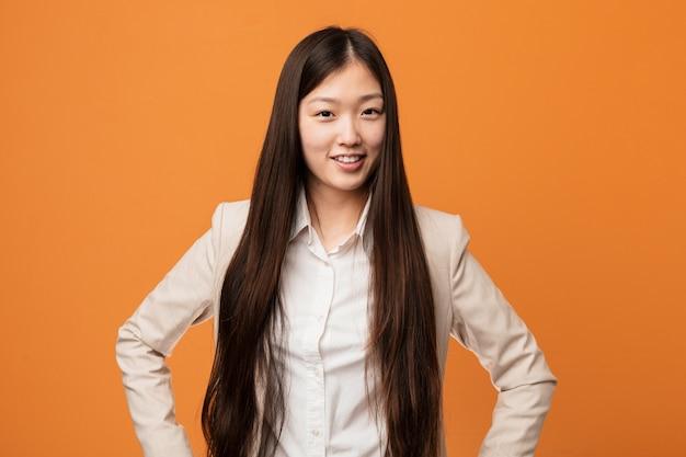 Mulher chinesa de negócios jovem confiante mantendo as mãos nele quadris