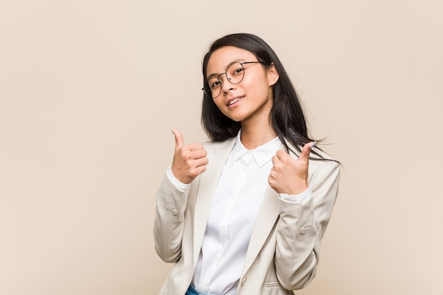 Mulher chinesa de negócios jovem, levantando os dois polegares, sorrindo e confiante.