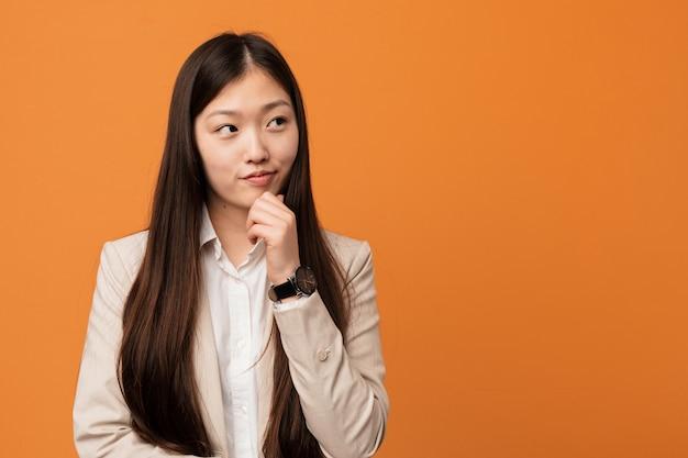 Mulher chinesa de negócios jovem olhando de soslaio com expressão duvidosa e cética.