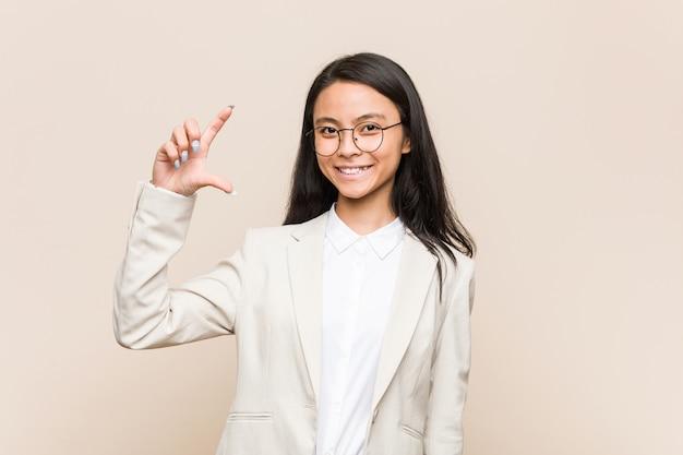 Mulher chinesa de negócios jovem segurando algo pouco com o dedo indicador, sorrindo e confiante.