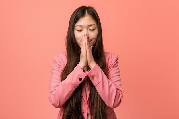 Mulher chinesa de negócios jovem vestindo terno rosa de mãos dadas para orar perto da boca, sente-se confiante.