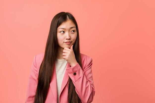 Mulher chinesa de negócios jovem vestindo terno rosa, olhando de soslaio com expressão duvidosa e cética.