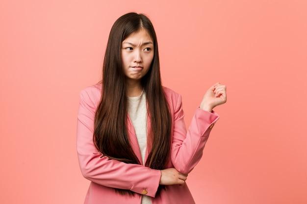 Mulher chinesa de negócios jovem vestindo terno rosa tocando a parte de trás da cabeça, pensando e fazendo uma escolha.