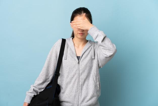 Mulher chinesa do esporte novo com o saco do esporte sobre os olhos azuis isolados da coberta pelas mãos. não quero ver algo