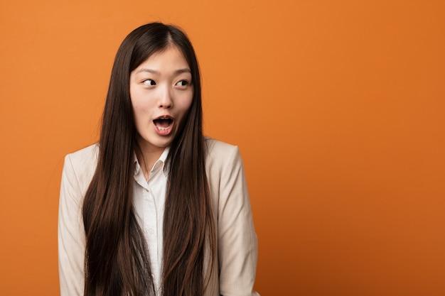 Mulher chinesa do negócio novo que está sendo chocada por causa de algo que viu.