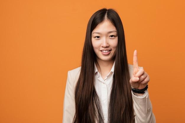 Mulher chinesa do negócio novo que mostra o número um com dedo.