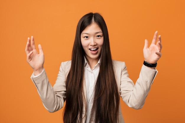Mulher chinesa do negócio novo que recebe uma surpresa agradável, entusiasmado e levantando as mãos.